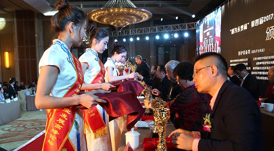 颁奖典礼现场礼仪小姐为获奖企业送上奖杯和荣誉证书